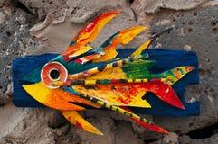 Pannello di legno con il pesce che appende sulle rocce nere Fotografia Stock
