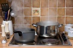 Pannen die in een keuken koken stock foto