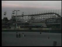 Panning amusement park by beach at dusk stock video