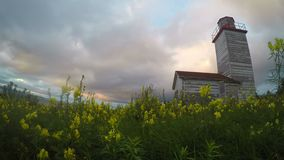 Panning Canadian Lighthouse time-lapse. Panning time-lapse clip of old wooden Canadian light house in Cape Breton against a backdrop of wind-blown sunset clouds stock footage