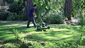 Panning down to turning mower. Young man turns lawn mower around in green lawn stock video