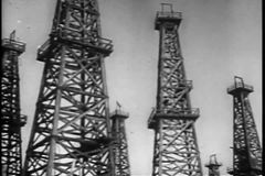Panning low angle view distillation towers in oil field stock video footage