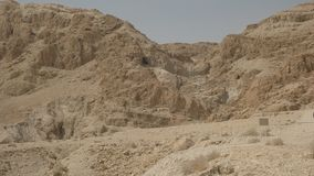 Panning mening van de heuvels en de holen die de dode overzeese rollen bevatten bij qumran stock footage