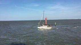 Panning met een voorbijgaande Zeilboot die op de Noordzee, het Oosten Frisia, Duitsland varen Geschoten van een veerboot stock videobeelden