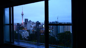 Panning motion over a widow with view of Auckland city skyline at dusk stock footage