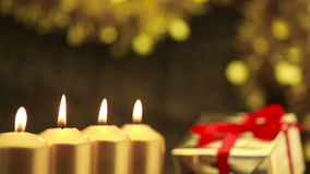 Panning over four advent candles at christmas. With gift in background stock video footage