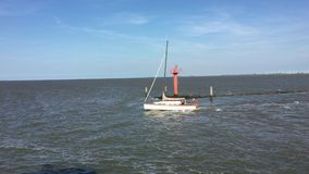 Panning with a passing Sailboat sailing on the North Sea, East Frisia, Germany. Shot from a ferry. stock video footage