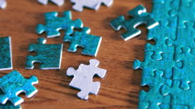 Panning from puzzle pieces to complete puzzle stock video footage