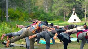 Group of people doing yoga outside. stock footage