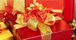 Panning scene video of red gift box. Panning scene video of red gift box decorated by golden and red bow, among pile gift boxes, concept for Christmas or stock video