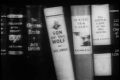 Panning shelf filled with books written by Jack London stock video footage