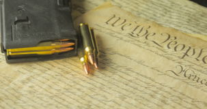Panning Shot of Ammunition Lying on the Constitution of the USA stock video footage
