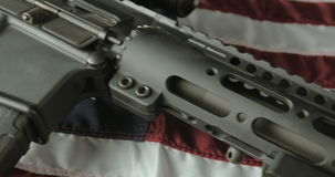 Panning Shot of an Assault Rifle Lying on an American Flag stock video footage