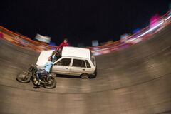 Panning shot of  bike and car driving inside death well