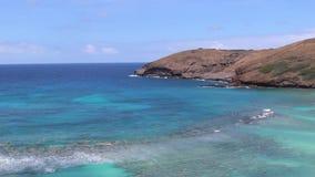 Panning shot of Hanauma Bay beach with coral, blue and green sea, Oahu, Hawaii. Panning shot Hanauma Bay Nature Preserve with coral, blue-green ocean waters stock video footage