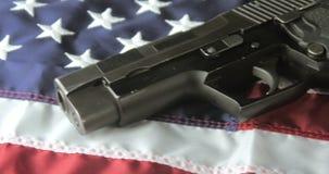 Panning Shot of a Handgun Lying on an American Flag stock video