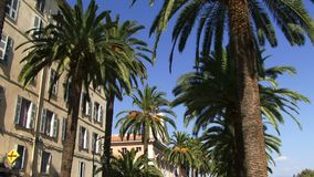 Panning shot of the main high street Corsica. Buildings in Corsica with palm trees stock video footage