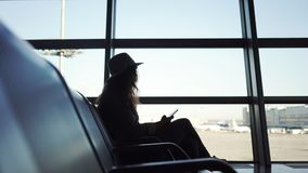 Girl sitting in airport. Panning shot through modern seats in airport waiting zone. Side view of young lady in silhouette sitting and holding smartphone opposite stock video footage