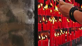 Panning shot on people burning candles. Chinese Buddhist temple in Kunming. Although Chinese society is predominantly atheist, the number of practising Buddhist stock footage