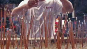 Panning shot on people burning incense sticks in a temple. Chinese Buddhist temple in Kunming. Although Chinese society is predominantly atheist, the number of stock video footage