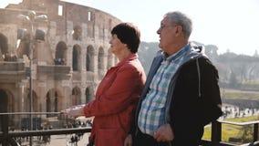 Panning strzał romantyczna starsza szczęśliwa Europejska para stoi wpólnie przy kolosseumem na wakacje w Rzym, Włochy zbiory wideo