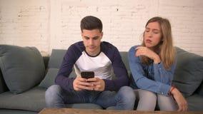 Panning strzału młodego człowieka używa ogólnospołecznych środki na telefonie komórkowym ignoruje jego dziewczyny kanapy leżankę  zdjęcie wideo