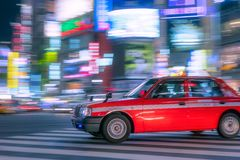 Panning taxi by night with colorful lights in the background. Japanese panning taxi traffic in motion blur by night with vivid and colorful lights and light Royalty Free Stock Photo