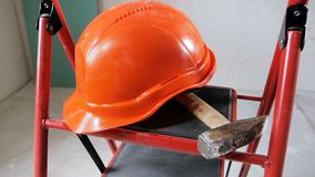 Panning van de close-up langzame motie video die van hamer en bouwvakker op metaaltrapladder binnenshuis liggen in aanbouw of stock video