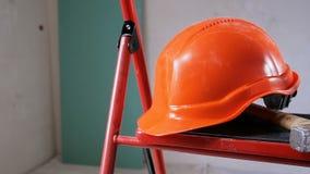 Panning van de close-up langzame motie video die van hamer en bouwvakker op metaaltrapladder binnenshuis liggen in aanbouw of stock videobeelden