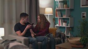 Panning van de mens gebruikt een smartphone en negeert zijn meisje stock footage