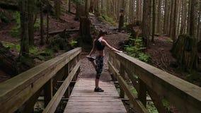 Panning van een jonge vrouw in zich sportsware het uitrekken op een houten brug in een altijdgroen bos met een stroom wordt gesch stock video