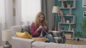 Panning van gelukkige vrouwenzitting op laag en het breien in huisworkshop stock videobeelden