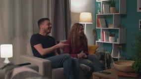 Panning van jonge gelukkige paarzitting op bank heeft en pret die babbelen lachen stock footage