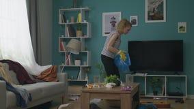 Panning van jonge vrouw doet het schoonmaken in de woonkamer na de partij stock footage