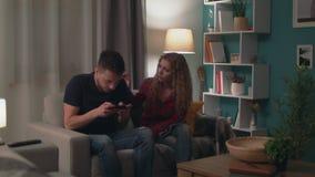 Panning van mensenspel in spel op smartphone en negeert zijn meisje stock videobeelden