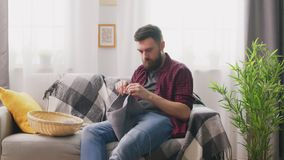 Panning van mensenzitting op bank en het breien bij comfortabel huis stock footage