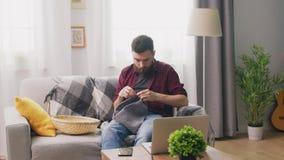 Panning van mensenzitting op bank en het letten op het breien leerprogramma op laptop stock video