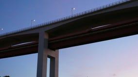 Panning van onderaan van de iconische 25 April-brug in Lissabon, Portugal bij zonsondergang met magenta en roze kleuren bij blauw stock video