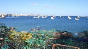 Panning van schaaldierenvallen bij Cascais-Baai, Portugal met vissersboten op achtergrond stock videobeelden
