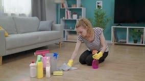 Panning van vrouw in gele handschoenen met doek schoonmakende vloer in woonkamer stock videobeelden