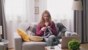 Panning van vrouwenzitting op bank en het breien bij comfortabel huis stock footage