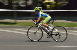 Panning of a very young boy riding bicycle in a sunny day, competing for Road Grand Prix event, a high-speed circuit race Royalty Free Stock Photography