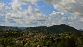 Panning video of clouds over residential homes in Happy Valley OR early fall HD. High definition panning video of white clouds and blue sky over residential stock video footage