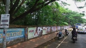 Advertising on a wall. Panning, wide shot of cars passing by a long wall filled with posters and advertising stock footage