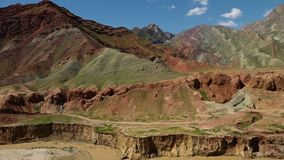 Red and green hills. A panning, wide shot of vivid mountains and hills, coloured in red, yellow and green stock video footage