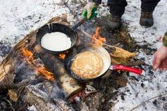 Pannkaka som lagas mat på en brand i en stekpanna med en röd penna Arkivbilder
