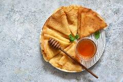 Pannkakavecka Tunna pannkakor med honung på köksbordet ovanför sikt royaltyfria bilder