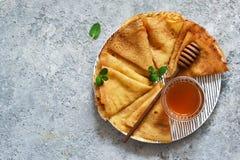 Pannkakavecka Tunna pannkakor med honung på köksbordet ovanför sikt fotografering för bildbyråer