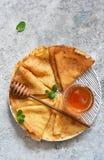 Pannkakavecka Tunna pannkakor med honung på köksbordet ovanför sikt royaltyfri foto