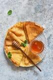 Pannkakavecka Tunna pannkakor med honung på köksbordet fotografering för bildbyråer
